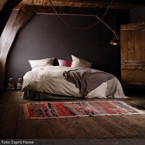 Erdige Brauntöne strahlen eine warme Atmosphäre aus: Die braune Wand, die Dielen und Tür aus Naturholz sowie walnussfarbige Holzbalken erwecken einen afrikanischen Touch und lassen das Schlafzimmer dunkel erscheinen. Die hellen Bettbezüge lockern das Ambiente auf und schaffen mittels des archaischen Teppichs und der Hängelampe einen natürlichen Ethno-Look.