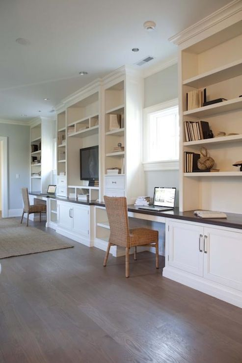 Office with wall to wall built-in and desks with black countertops and seagrass desk chairs. Open shelving and hardwood floors.