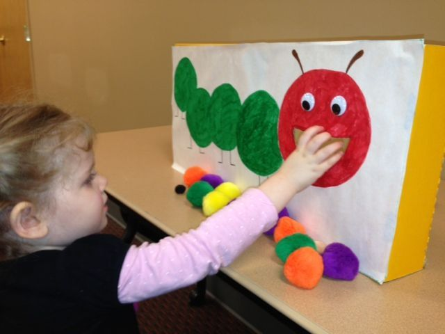 """The children had fun ""feeding"" the hungry caterpillar a variety of colors and sizes of pompoms. This encouraged even my little ones to recall the food from the story – they called the purple pompoms ""plums,"" the red ones were ""apples,"" etc."""