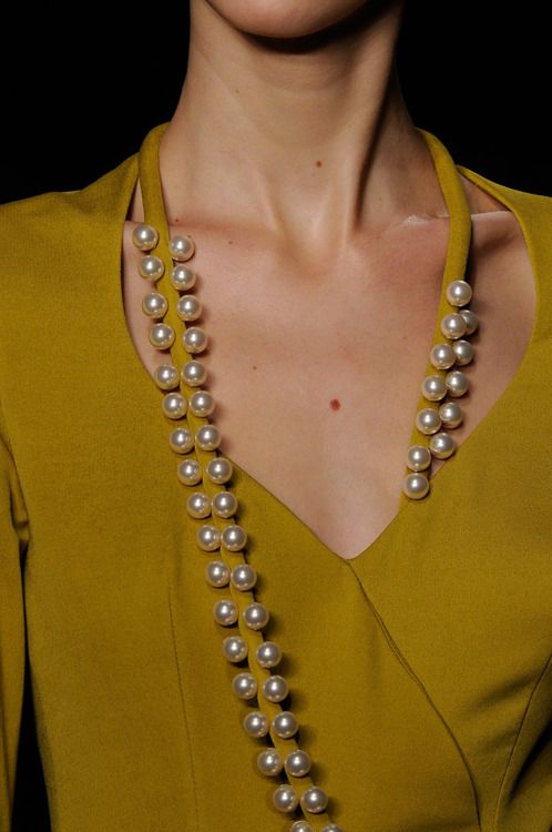 "This is an interesting design that incorporates an accessory into the dress. This design makes it easier for a woman who is unsure of how to style her outfits. Now she has her dress and ""necklace"" covered."