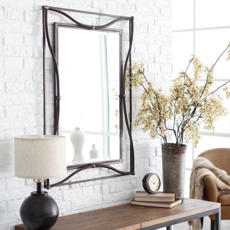 Oglindă cu ramă elegantă, deasura unei console în living.