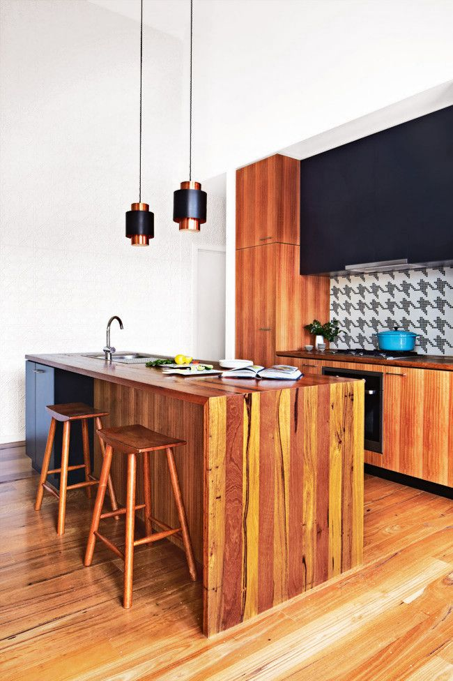 2. A white pressed-metal feature wall creates subtle interest, contrasting with the smooth, cylindrical pendant...