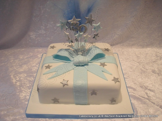White blue and silver celebration birthday cake decorated with silver shimmered stars. Topped with an icing ribbon and bow surrounding a wired star and feather explosive topper
