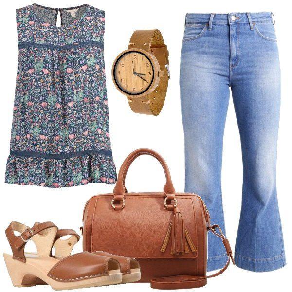 I jeans a vita alta, 7/8 e larghi sul fondo, sono abbinati alla blusa senza maniche con scollo tondo in viscosa a fantasia floreale. Ai piedi i sandali in pelle con tacco a cono in legno. La borsa a mano è in fintapelle. L'orologio è in legno naturale di bambù.