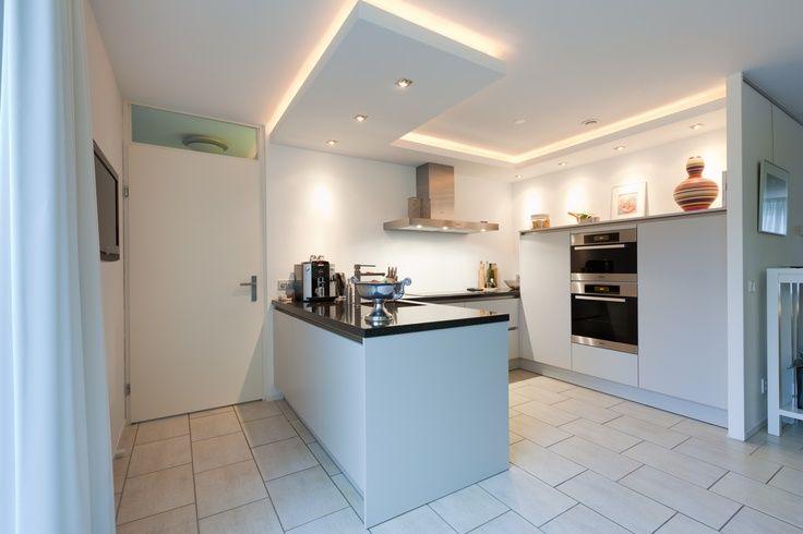 Greeploze keuken met schiereiland en koof met indirecte verlichting — in Dordrecht, Zuid-Holland.:
