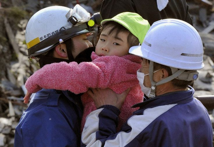 Rescue workers hold a girl they rescued from a building after the tsunami and earthquake in Kesennuma on March 12, 2011.