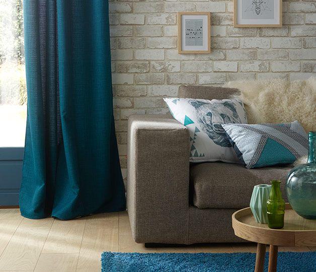 Un salon dynamisé par des touches de bleu canard. Des rideaux au tapis en passant par les coussins...