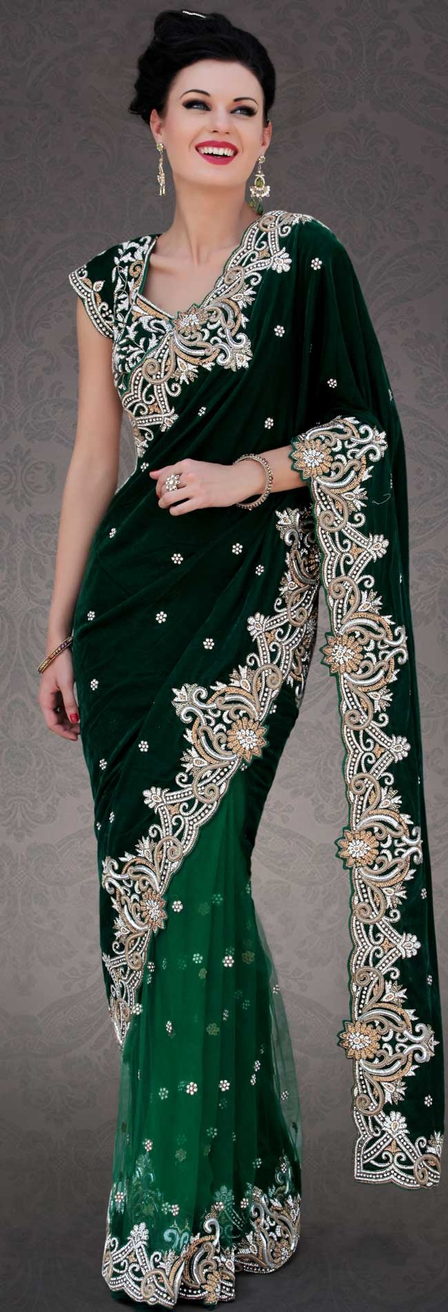 Different colors are a perfect blend of traditional Indian heritage and contemporary artwork.   This dark green velvet and net saree is nicely designed with embroidery patch work is done with stone, zardosi and cutbeads work.   Beautiful embroidery work on saree make attractive to impress all.   This saree gives you a modern and different look in fabulous style.   Matching blouse is available.   Slight color variations are possible due to differing screen and photograph resolution.