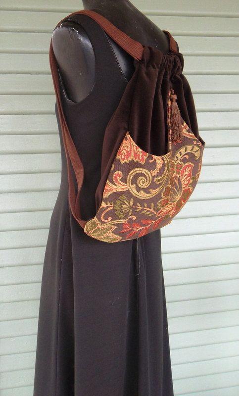 Original mochila hecha a mano hecha con terciopelo de algodón marrón. El bolsillo exterior es un rico tapiz de flores de naranja, verde y marrón de arcos en el centro y cosido en el punto. Este bolsillo exterior está forrado con satén. La bolsa sí es serged en el interior y mide 14 x