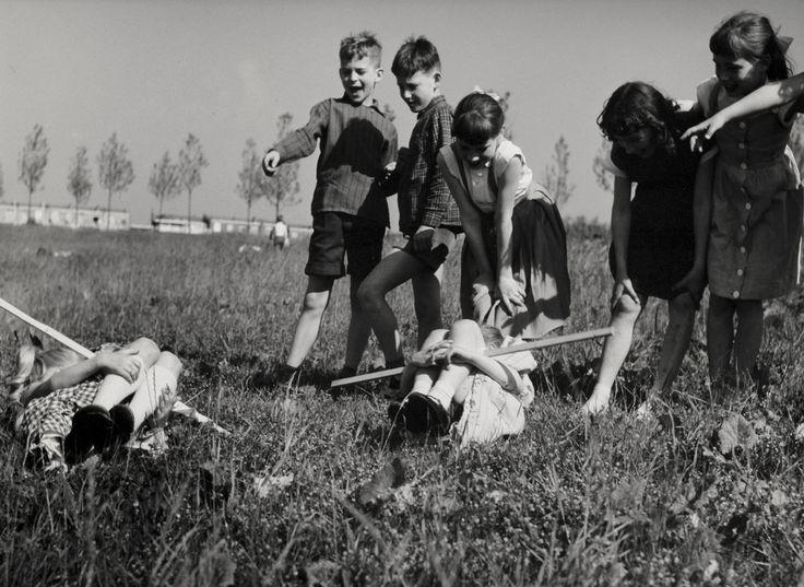 Kinderen, buiten spelen in een weiland. In het gras liggen twee meisjes met een stok onder de opgetrokken knieen. Op de achtergrond nieuwbouwhuizen. Nederland, 1950-1960.