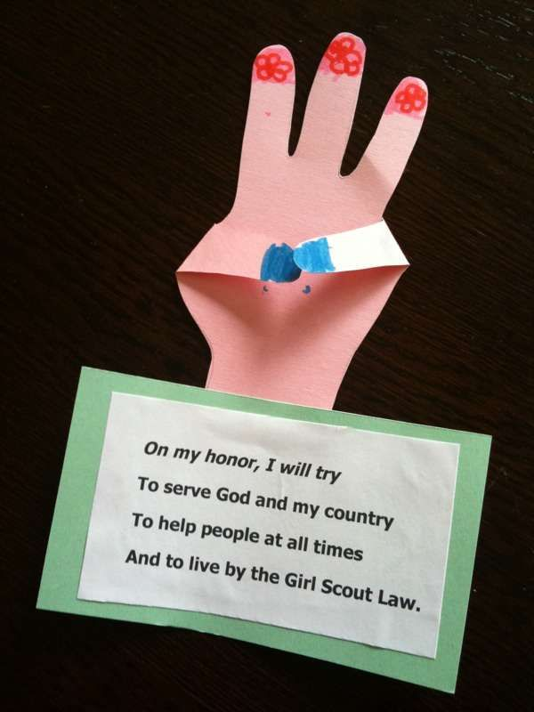 Although this has the American Girl Scout Promise on it I like the idea of the hand.  We could get the girls to draw round their own.