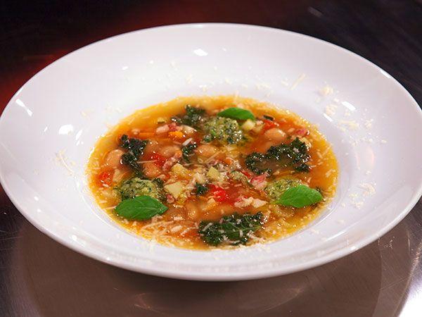Minestronesoppa med bönor som serveras med pesto och riven parmesan.