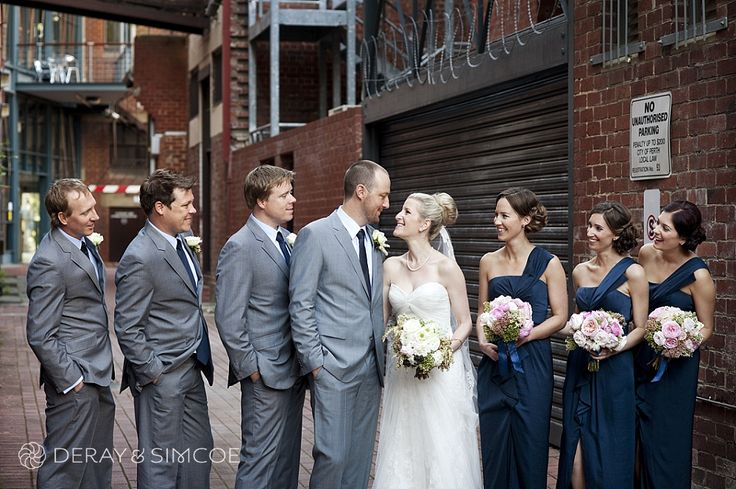 Urban wedding photos. Modern bridal party. Bridesmaids dressed in navy blue with pastel bouquets and groomsmen dressed in grey suits. Location ~ King Street, Perth  Photography by DeRay & Simcoe