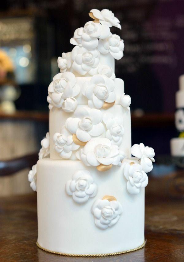 Tarta de bodas escalonada con 'fondant' de color blanco mármol, con camelias de azúcar en el mismo color. Obra de la pastelería Sugarplum en París (Francia).