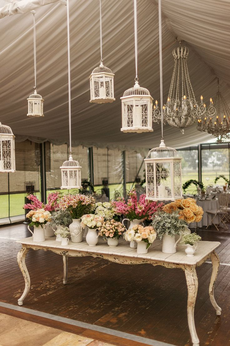 Look how romantic this wedding decor is! Eclectic Pitchers and Container after container of lovely blooms plus chandeliers and birdcages and everything else romantic you can fit in a tent! Makes me want to keep exploring!!  See More here:  http://www.StyleMePretty.com/australia-weddings/2014/04/02/romantic-garden-wedding-at-the-james-terrara-house/ At Dusk Photography - atdusk.com.au/
