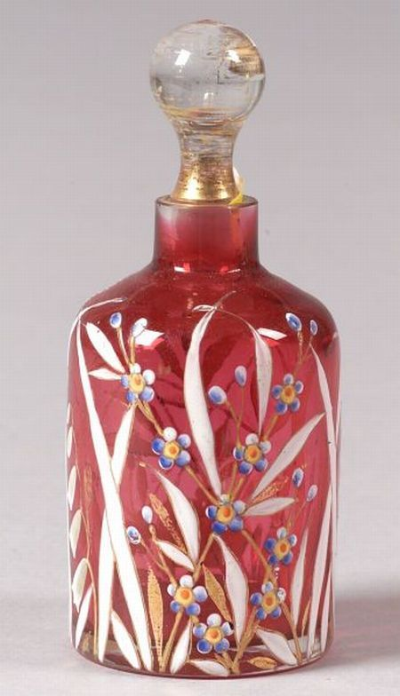 Art Nouveau  Enameled glass perfume  Europe, late 19th century  Decorated with blue flowers with orange centers with white leaf blades, gilt accents on cranberry red glass, colorless glass stopper, some gilt wear, ht. 4 3/4 in.