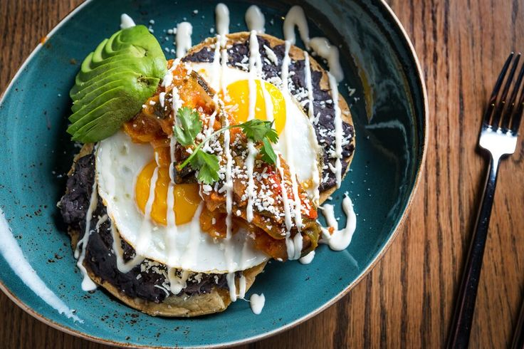 Huevos Rancheros: Two Sunny-Side Up Eggs, Corn Tortilla, Avocado, Refried Black Beans, Cotija Cheese, Salsa Ranchera