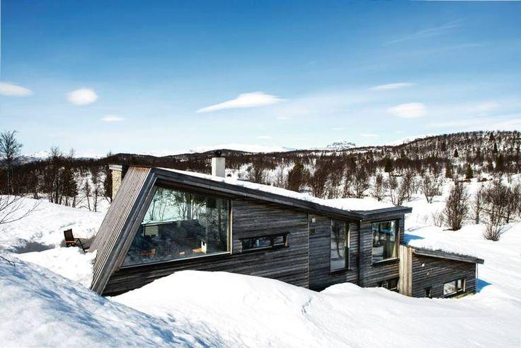 SKRÅTT STILT: Hytta sklir naturlig inn i fjellmiljøet og på grunn av de store vindusflatene har man godutsikt til den vakre naturen også når man er inne.Hytta er tegnet av arkitekt Cecilie Wille hos Morfeus Arkitekter.