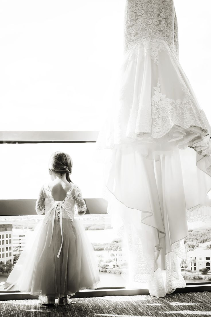 Adorable wedding photo idea to have the flower girl standing next to the bride's dress. Even better in black and white! (Limelight Photography)