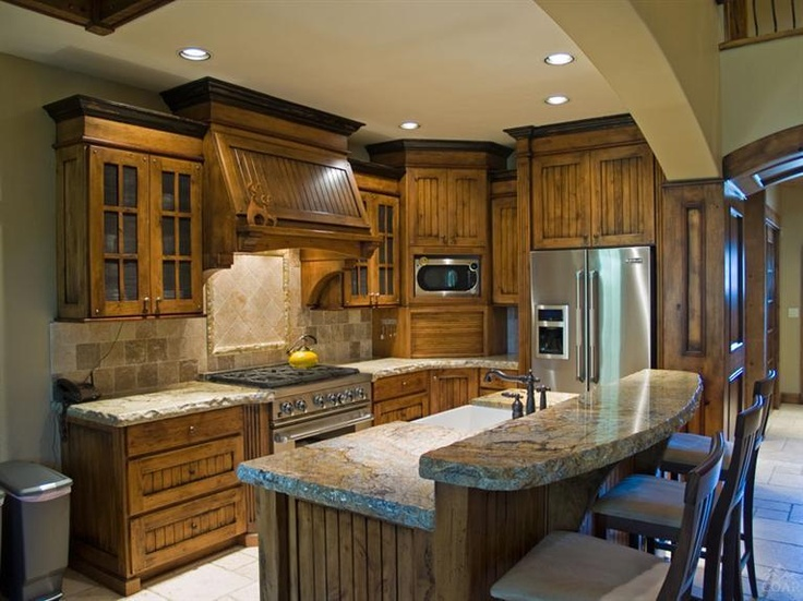 Custom knotty alder wood cabinets and hood Travertine