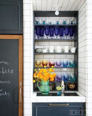 Colorful glassware looks gorgeous on display in a white kitchen