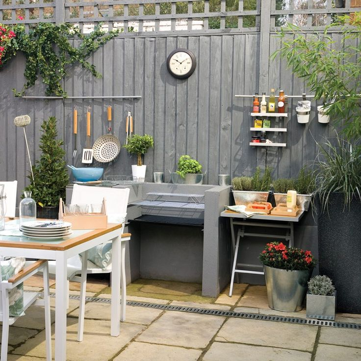 Garden fence painted grey with cooking station - Use your garden fence as part of an outdoor kitchen. Hang utensils in close reach of the action, along with a rack for all your favourite sauces. You could even place a clock on the 'wall', so you can make sure your burgers and steaks don't get cremated.