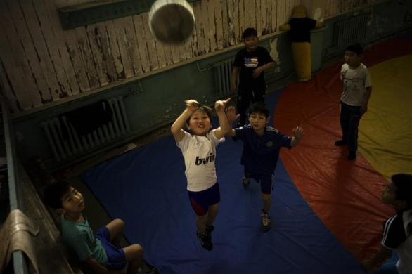 Children play basketball at a gym which they share with Mongolia's Olympic freestyle 60kg wrestler Mandakhnaran Ganzorig in Ulan Batur, October 27, 2011.  REUTERS/Kieran Doherty