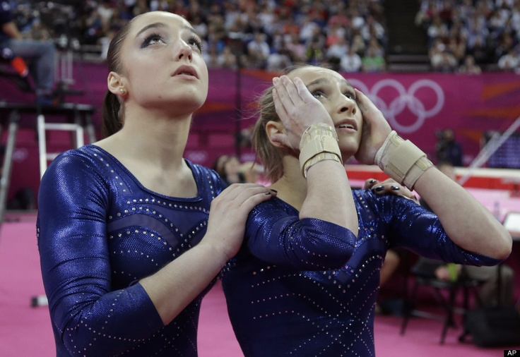 Russian gymnast Aliya Mustafina, left, and teammate Victoria Komova look up at the score display as they wait for the declaration of results during the artistic gymnastics women's individual all-around competition at the 2012 Summer Olympics, Thursday, Aug. 2, 2012, in London.