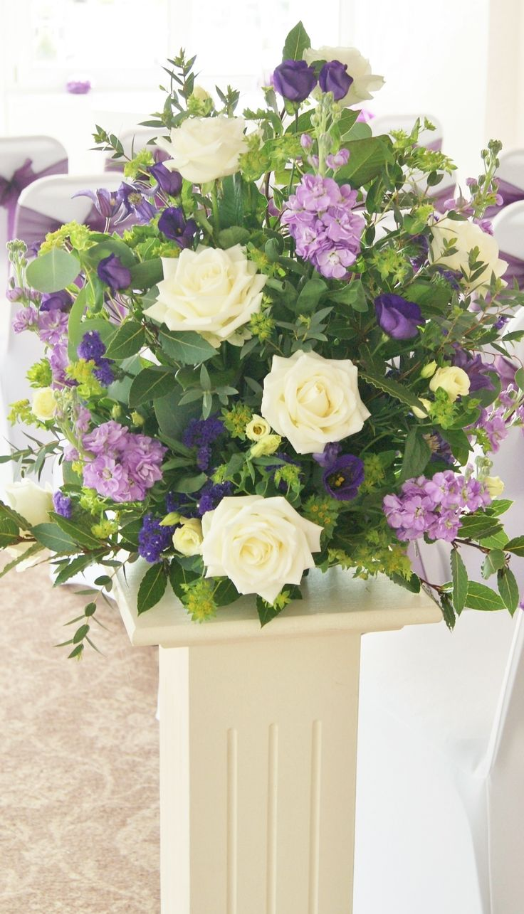 Florissimo, Shropshire - Flowers for weddings, events and businesses. Wedding pedestal flowers display of white avalanche roses, purple lisianthus, white lisianthus, purple statice, purple stock, purple clematis, green bupleurum and eucalyptus.