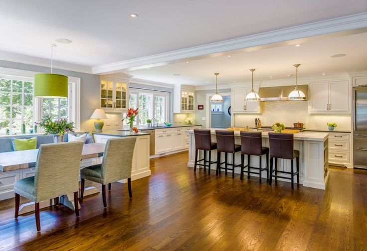 kitchen with white oak flooring, white island, white cabinet and backsplash, dark stools, white book dining seat with green chushion, green lamps, white pendant lamps of Large Space in the Kitchen for More People and More Warmth