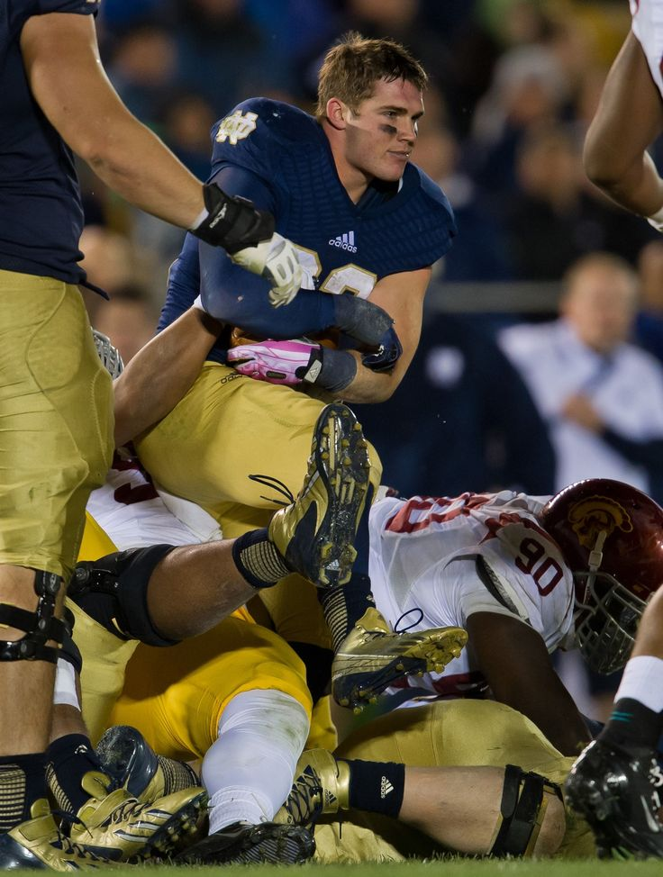 Cam McDaniel #33 of the Notre Dame Fighting Irish gets tackled after losing his helmet against the University of Southern California Trojans at Notre Dame Stadium on October 19, 2013 in South Bend, Indiana. Notre Dame defeated USC 14-10.