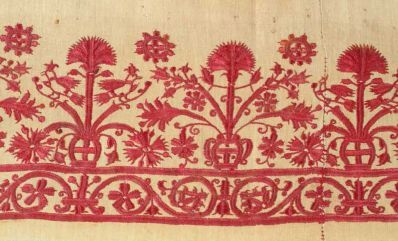 A white cotton skirt border embroidered with crimson red silk depicting birds atop flowering shrubs. Crete, Greek Islands, 18th c., silk on cotton,