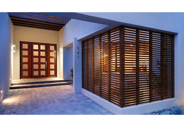 Exterior view of the entry with a trellis above and a wood screen giving privacy to the street-facing guest bedroom.  A contemporary house in style.  Stucco siding, wood screen and trellis, and flat roofs.
