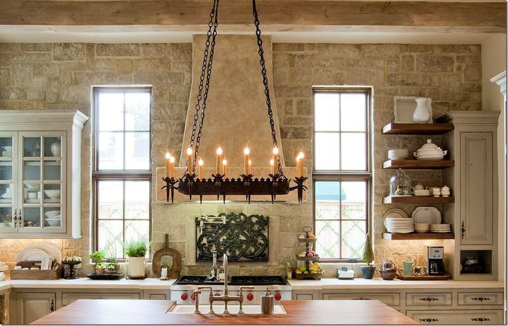Here's a closeup of the cooktop with its stone hood and stone wall.  I love the stone!!!  The countertops are limestone – and the island is wood.  Pretty open shelves on the right side.
