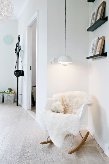 bedroom idea: chair with sheepskin on it and lamp next to it