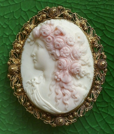 GODDESS FLORA         Materials: shell, gold (Unmarked)  Size of the cameo: 1 3/4 x 1 5/16  Size of the frame: 2 1/4 x 1 15/16  Date and origin: England, ca 1850-70.  Condition: mint.        Magnificent goddess Flora.  The flowers on her hair are magnificent and luxuriant, carved in very high relief.  Pink shell cameos of high quality are very rare.