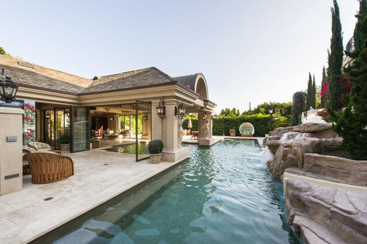The open, airy poolhouse partially covers one of the home's pools, offering some privacy and shade. A waterfall flows into the uncovered part of the pool to complete the elegant pool design.