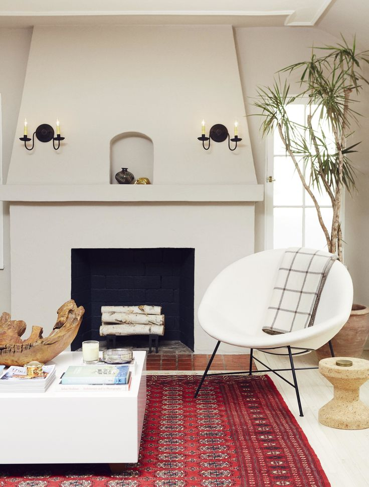 The classic Spanish Revival style fireplace was pleasantly uncovered during the renovation. Farrow & Ball's Elephant's Breath was painted on the plaster hearth, with a chic pop of black on the interior. In front, a vintage half-moon chair is arranged beside a cork stool from Hive Modern.