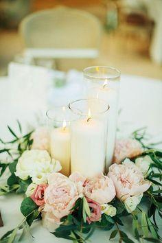 Beautiful wedding centerpiece made of candles in cylinder vases and pastel pink peonies and ivory roses | Très beau centre de table composé de bougies dans des vases cylindriques, de pivoines rose pastel et de roses ivoire.