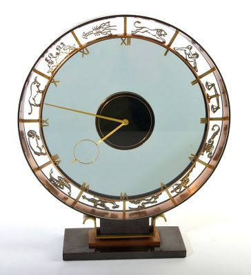 """This is what we like to refer to as Art Deco Deluxe. Bronze signs of the zodiac encircle a smoked glass face. This is a handsome timepiece from an elegant era gone by. We feel strongly that the 1920-30s definition of futurism makes perfect sense in the present. European in origin, likely French. Just under 10"""" in diameter."""
