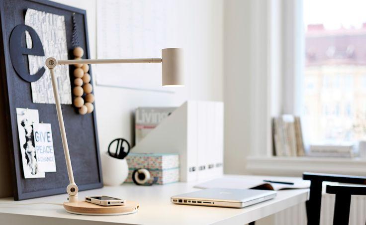Um escritório em casa com um candeeiro com carregamento sem fios sobre a secretária IKEA