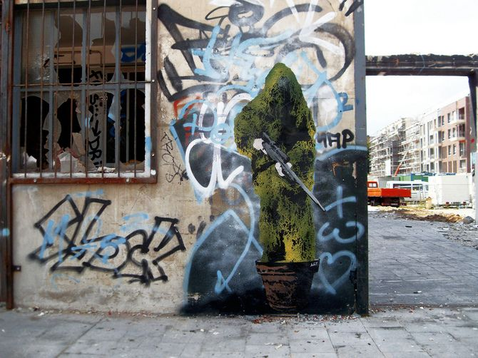 Sniper In Terracotta by l.e.t., in Dusseldorf,Germany. A stencil has been used, which must have taken to cut all the detail in it. It shows a possible soldier in camouflage , and the artist may be trying to send the message that society is surrounded by violence, and it is not alien in western countries. I selected it because looked funny and very random.