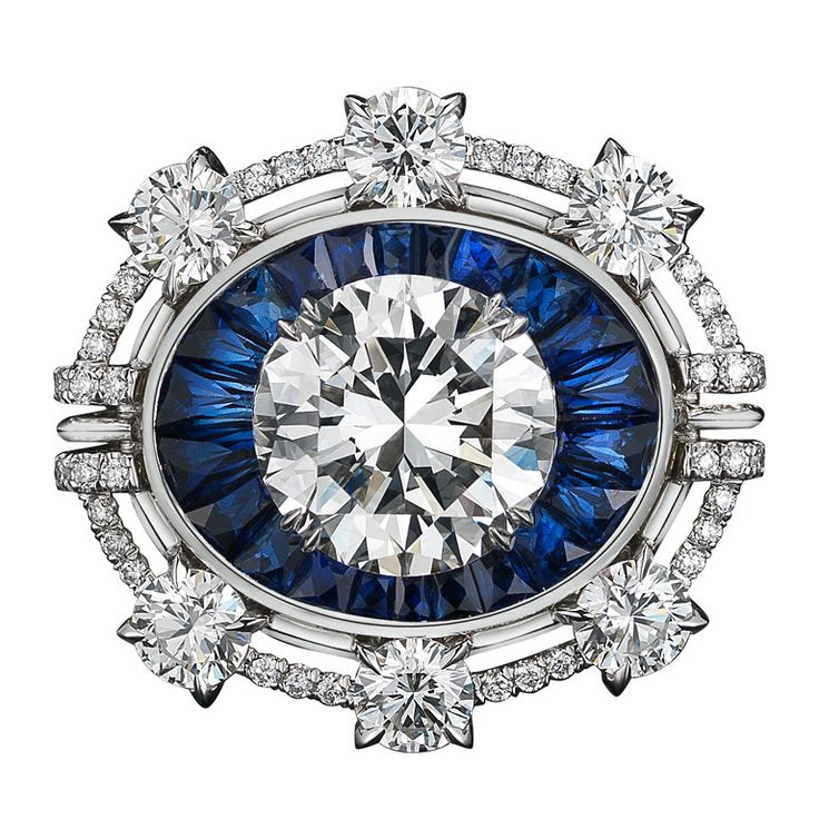 A one-of-a-kind Diamond ring comprised of 22 blue Sapphire Trapezoids totaling 2.80 carat weight and a 4.02 carat Brilliant-Cut Diamond floating in the center, surrounded by six 4mm round Diamonds, enhanced by Alexandra Mor signature details of 1mm knife edged-wire and 1mm floating Diamond melee.