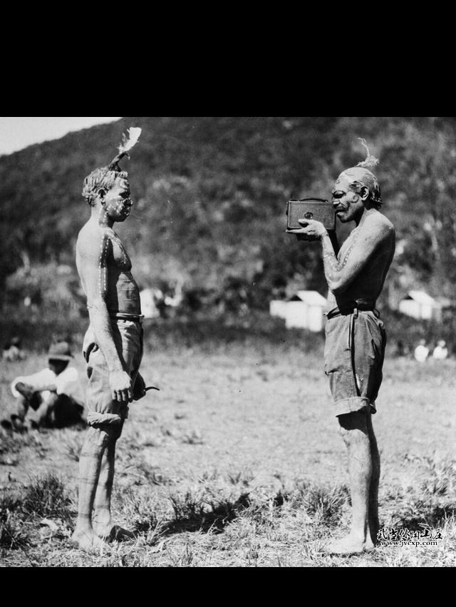 An Australian aborigine man photographs a fellow member of the tribe. Queensland, australia. 1929