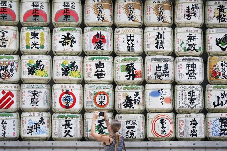 A tourist takes a photograph of a display of sake barrels at Meiji Shrine in Tokyo on May 6. The government plans to create a smartphone app that can scan sake labels to show related information in Japanese and English.