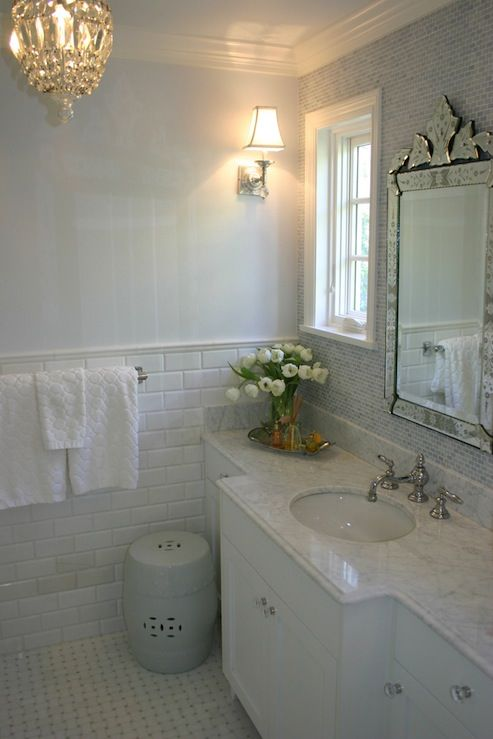 pale blue walls paint color, venetian mirror, beveled subway tiles backsplash, white bathroom cabinet with glass knobs, marble counter tops, white garden stool and basketweave marble tiles floor.