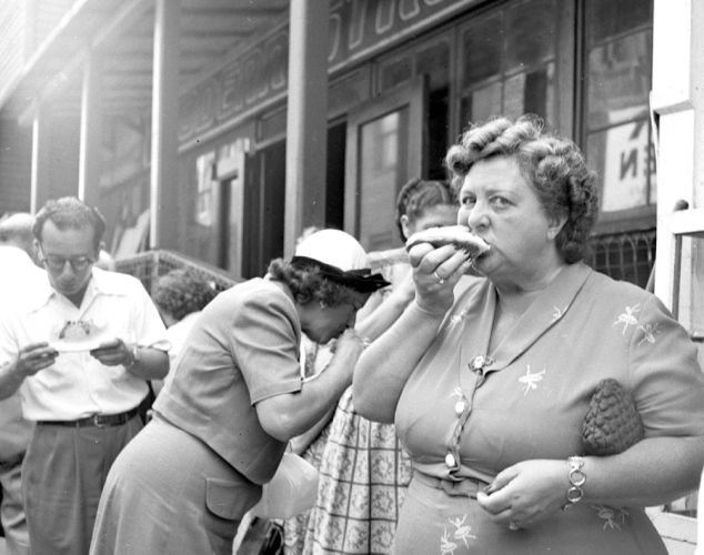 Woman eats a hot dog at Coney Island in 1950.