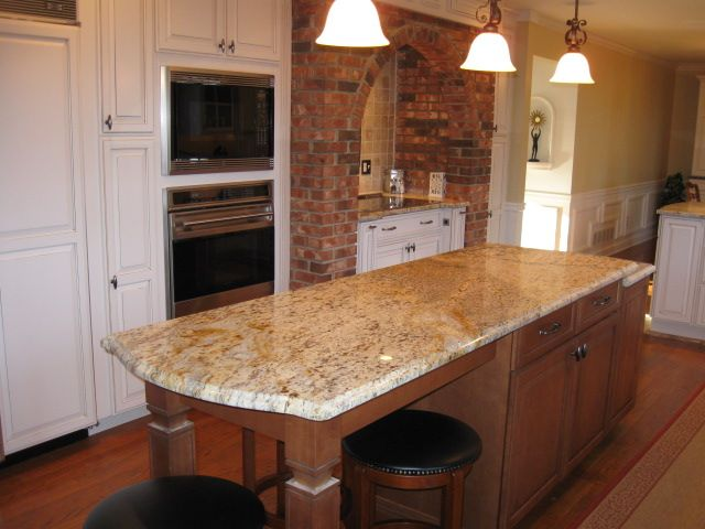 The long island that includes seating is just lovely. The warm use of brick gives the kitchen a traditional home feel.