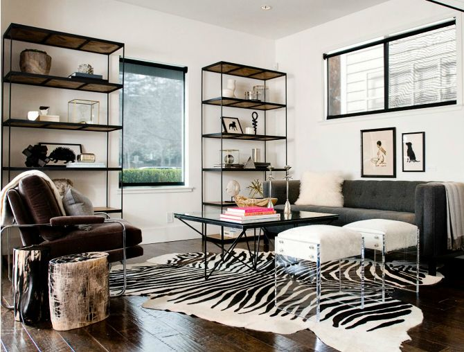 Kriste Michelini Interiors - living rooms - iron and wood bookcase, gray tufted sofa, acrylic stools, zebra cowhide rug, glass top coffee ta...