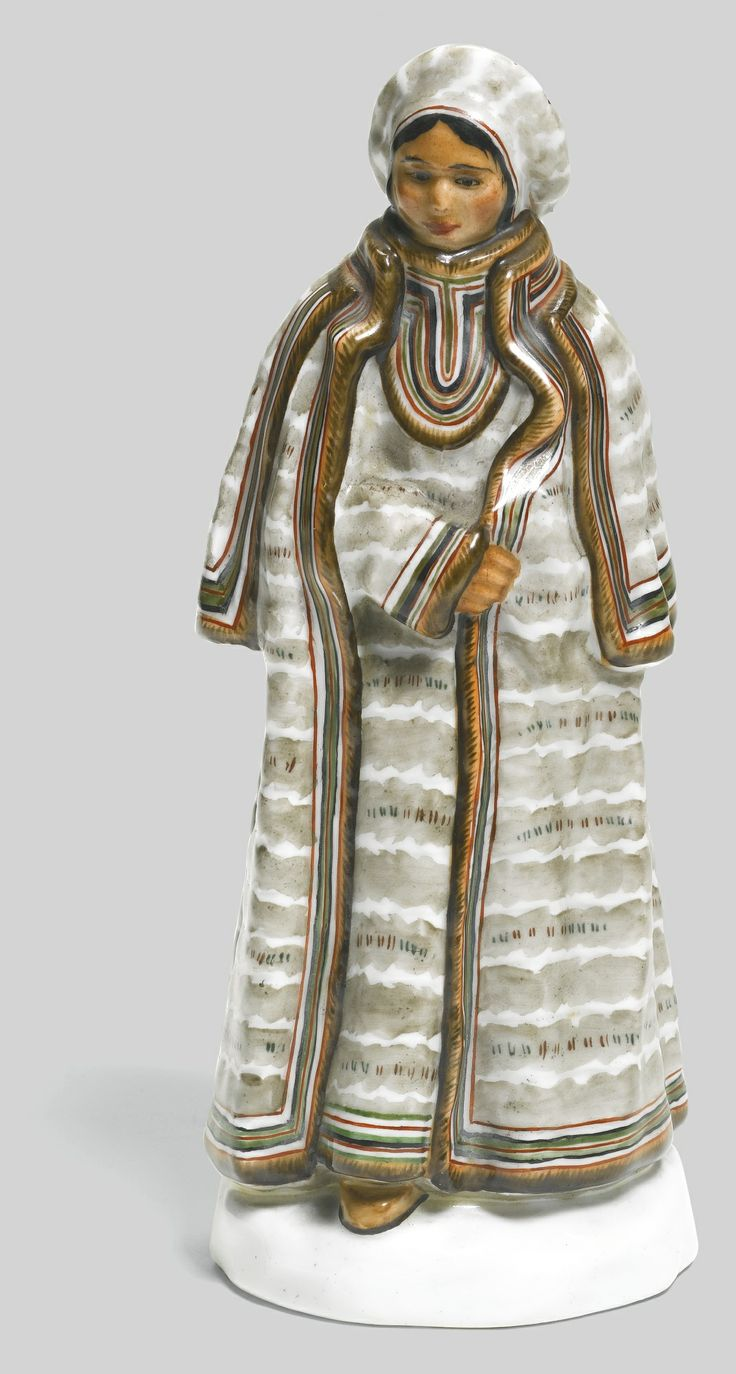 A SOVIET PORCELAIN FIGURE 'AN ALEUT WOMAN', STATE PORCELAIN MANUFACTORY, 1920S after a 1911-1913 model by Pavel Kamenskii for the series 'The Peoples of Russia', modelled as a standing Aleut woman dressed in fur robes and hat, with impressed factory mark in use from the 1920s-1936,  height 18.2cm, 7 1/8 in.